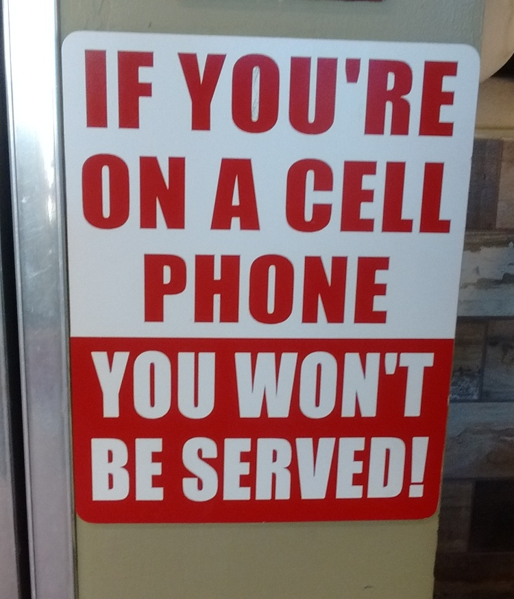 Sign at a local take-out shop. Risking their own business to do their parts to restore some semblance of civility to our technology-obsessed culture. Sign at a local take-out shop. Risking their own business to do their parts to restore some semblance of civility to our technology-obsessed culture.